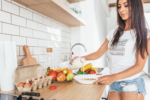 Mulher tomando café da manhã derramando leite em uma tigela com muesli na cozinha.
