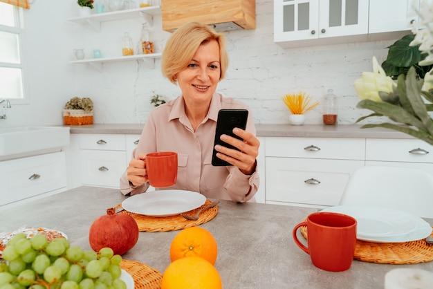 Mulher tomando café da manhã em casa com bolo de frutas e café e lê notícias no smartphone