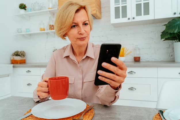 Mulher tomando café da manhã em casa e lendo no smartphone