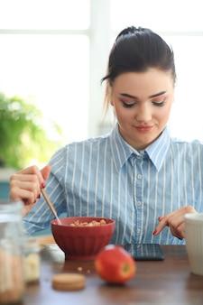 Mulher tomando café da manhã enquanto conversa com seu telefone
