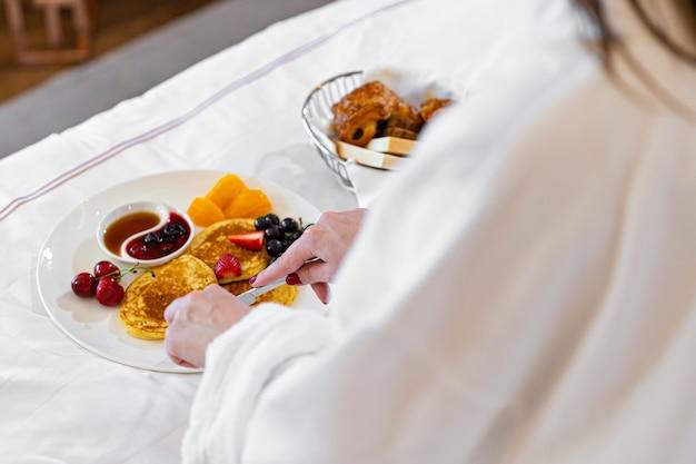 Mulher tomando café da manhã na cama. croissant de frutas frescas no prato