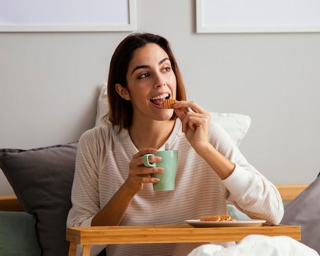 Mulher tomando café da manhã na cama em casa