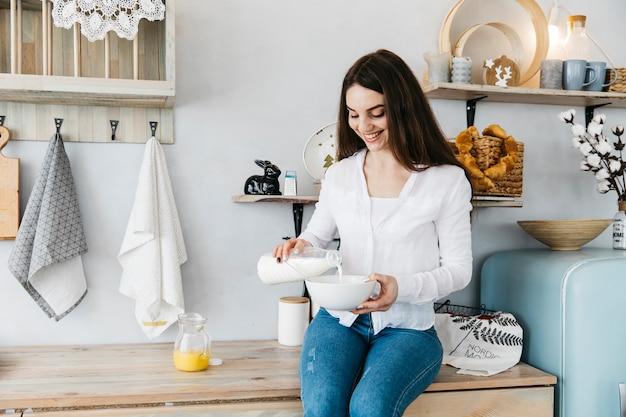 Mulher tomando café da manhã na cozinha