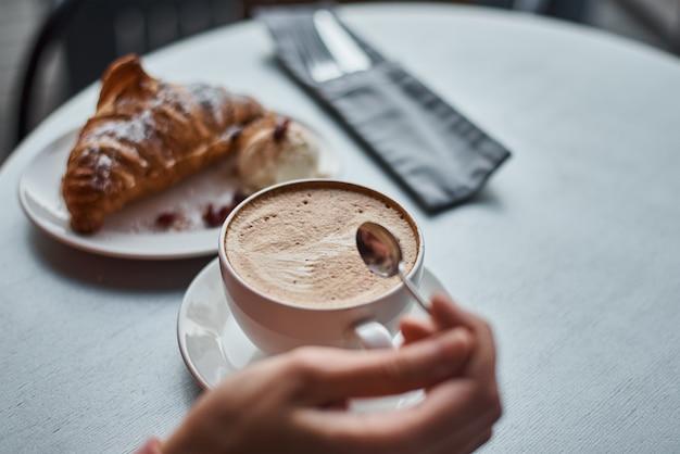 Mulher tomando café da manhã no café. xícara de café e croissant em uma mesa