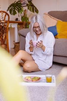 Mulher tomando café da manhã no chão