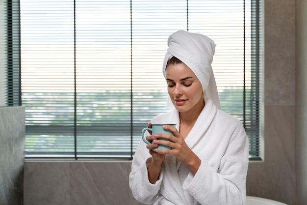 Mulher tomando café depois do banho
