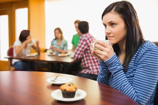 Mulher tomando café e bolinho no café