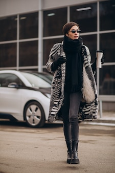 Mulher tomando café e carregando carro elétrico