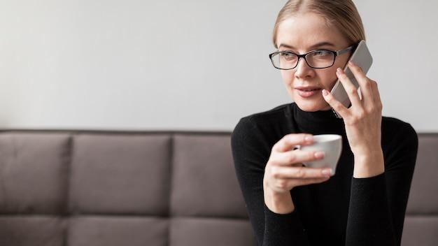 Mulher tomando café e falando por telefone