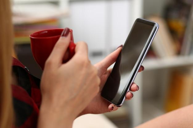 Mulher tomando café e olhando para smartphone