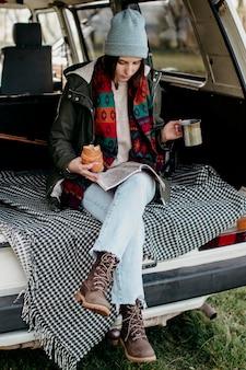 Mulher tomando café e olhando um mapa