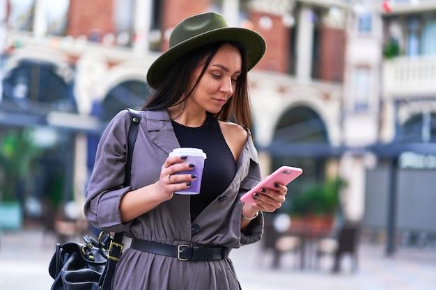 Mulher tomando café e usando smartphone durante uma caminhada no centro de uma cidade europeia