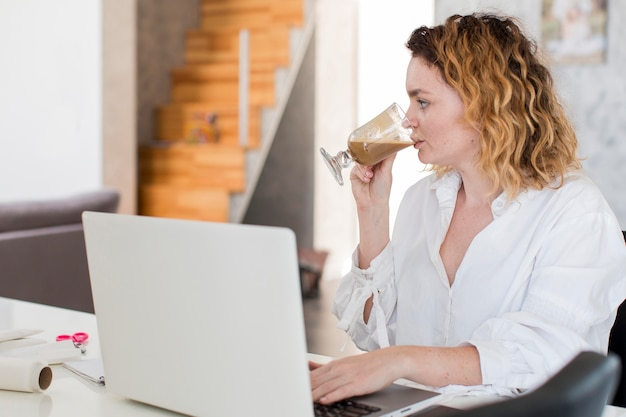 Mulher tomando café em casa