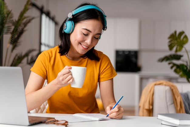 Mulher tomando café enquanto participava de uma aula online