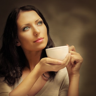 Mulher tomando café (foco nos olhos da modelo)