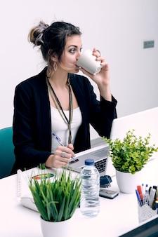 Mulher tomando café no local de trabalho