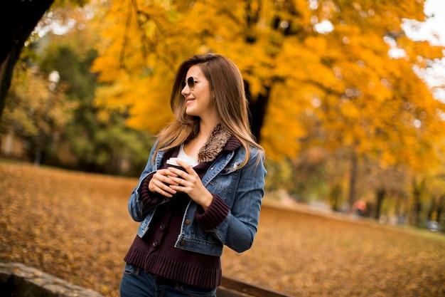 Mulher tomando café no parque outono