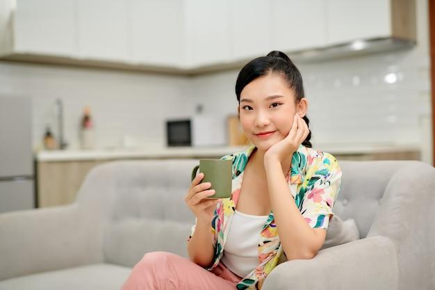 Mulher tomando café no sofá