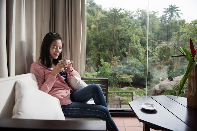 Mulher tomando café ou chá e pensando em casa