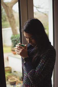 Mulher tomando café perto da janela de casa
