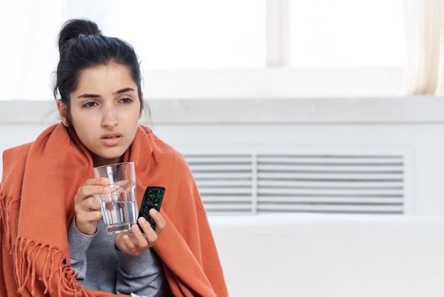 Mulher tomando cobertura com manta em descontentamento de tratamento de medicação em casa. foto de alta qualidade