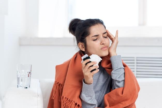Mulher tomando cobertura com manta no descontentamento de tratamento de medicação em casa. foto de alta qualidade