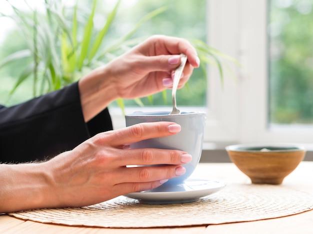 Mulher tomando colher de chá da xícara de chá