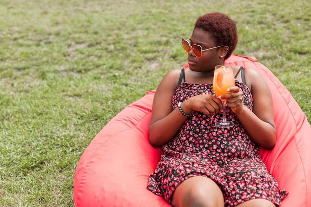 Mulher tomando coquetel ao ar livre no saco de feijão