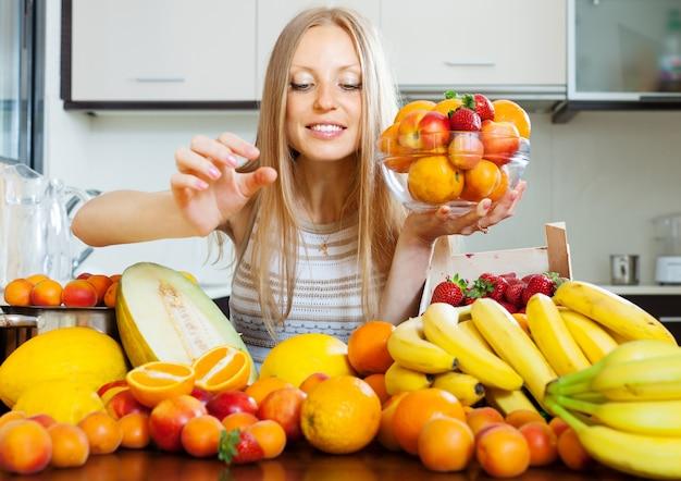 Mulher tomando frutas da mesa