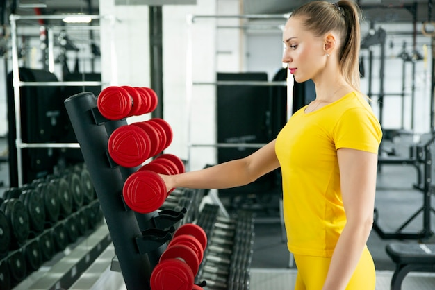 Mulher tomando halteres no ginásio fitness com halteres no rack