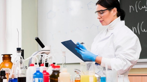 Mulher tomando notas em laboratório