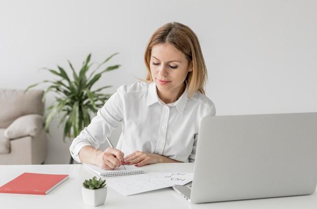 Mulher tomando notas em uma aula on-line