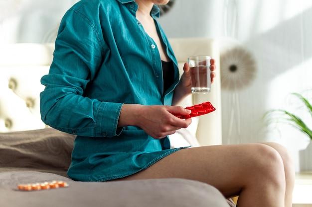 Mulher tomando o remédio e pílulas por causa de dor de estômago doloroso. pessoa que sofre de dor abdominal devido a menstruação e tpm. tratamento e terapia medicamentosa