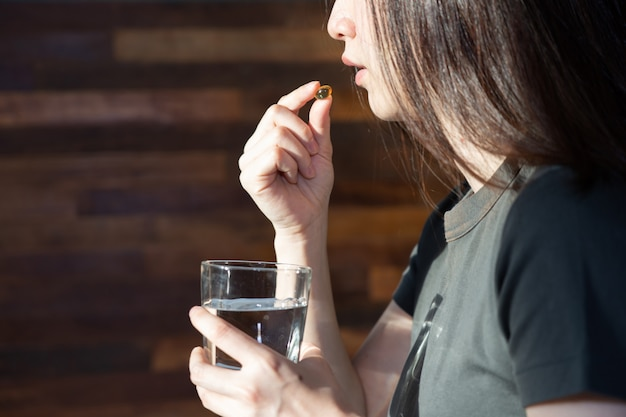 Mulher tomando pílulas com água devido a sua doença