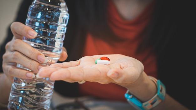 Mulher tomando remédio para curar doenças segurando uma garrafa de água