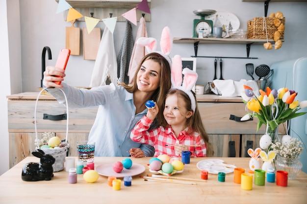 Mulher tomando selfie com filha perto de ovos de páscoa