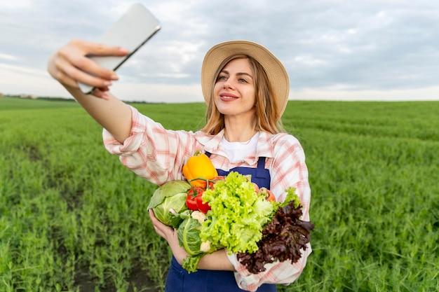Mulher tomando selfie com legumes