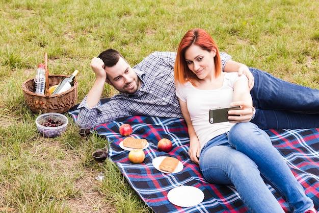 Mulher tomando selfie com o namorado no piquenique ao ar livre