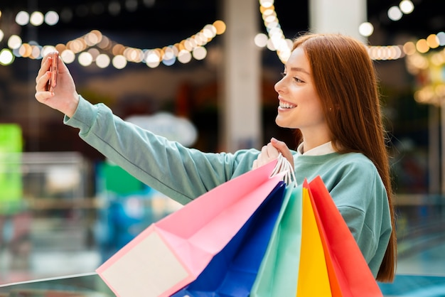 Mulher tomando selfie com sacolas de compras