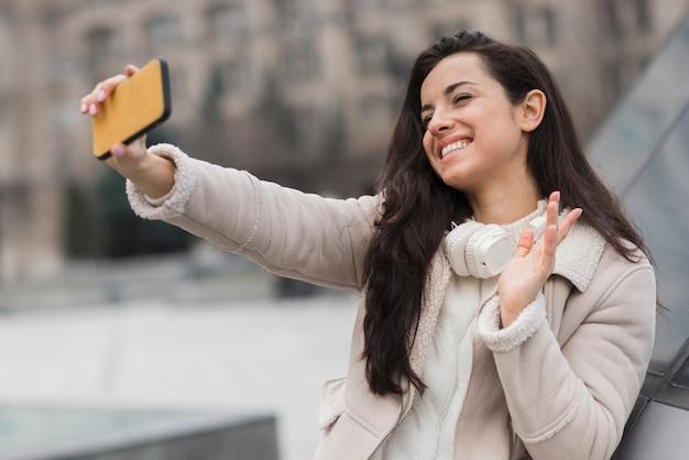 Mulher tomando selfie e acenando
