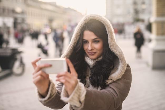 Mulher tomando selfie em pé na rua em tempo frio. moletom na cabeça.