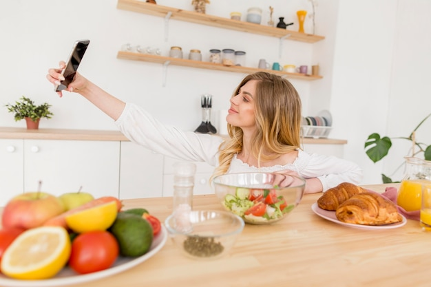 Mulher tomando selfie na cozinha
