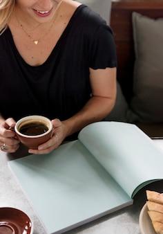 Mulher tomando um café enquanto lê uma revista