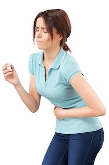 Mulher tomando um comprimido. feche a mão com um comprimido e a boca, isolada no fundo