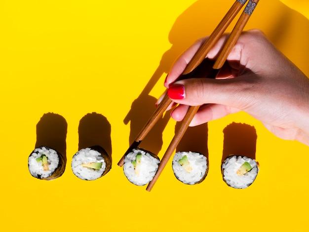 Mulher tomando um rolo nigiri de uma mesa amarela
