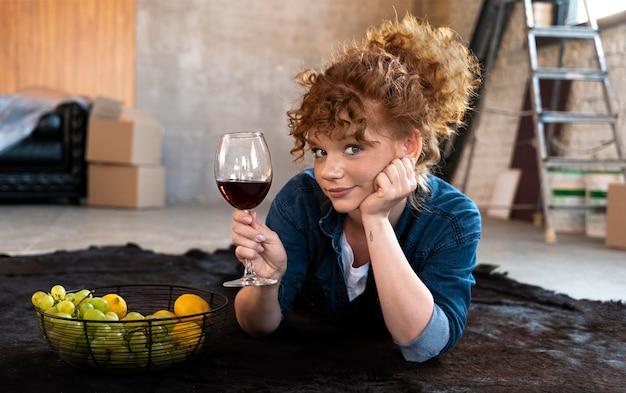 Mulher tomando uma taça de vinho em sua nova casa
