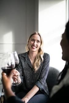 Mulher tomando uma taça de vinho tinto com amigos
