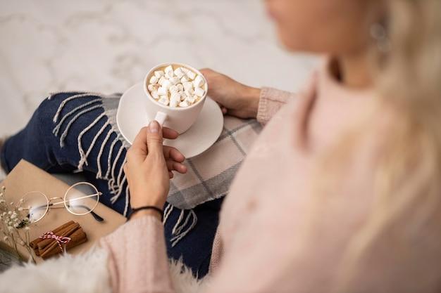 Mulher tomando uma xícara de chocolate quente com marshmallows enquanto lê