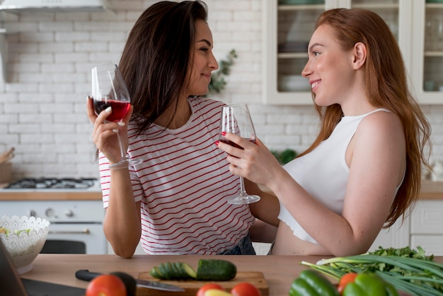 Mulher tomando vinho enquanto cozinha