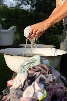 Mulher torce a roupa molhada depois de se lavar com as mãos na velha bacia ao ar livre no campo